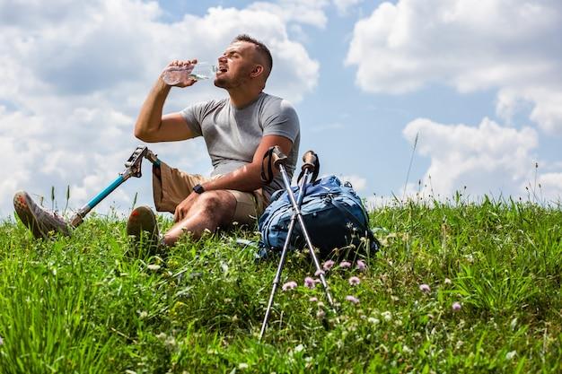 Aangename dorstige man die water drinkt terwijl hij op het gras rust na sportactiviteiten