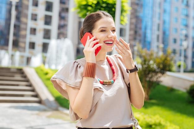 Aangename emoties. blije opgetogen vrouw die lacht tijdens het beantwoorden van een telefoontje