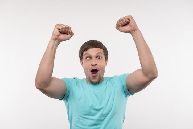 Aangename emoties. vrolijke positieve man juichen met zijn handen terwijl hij zich gelukkig voelt