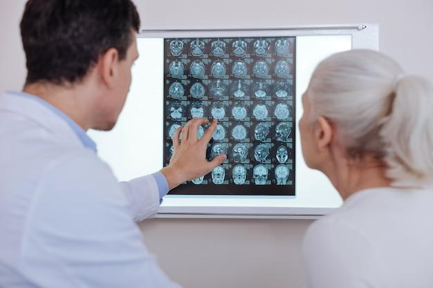 Aangename ervaren mannelijke arts die zijn patiënt een reeks röntgenfoto's laat zien en naar een ervan wijst terwijl hij haar diagnose uitlegt