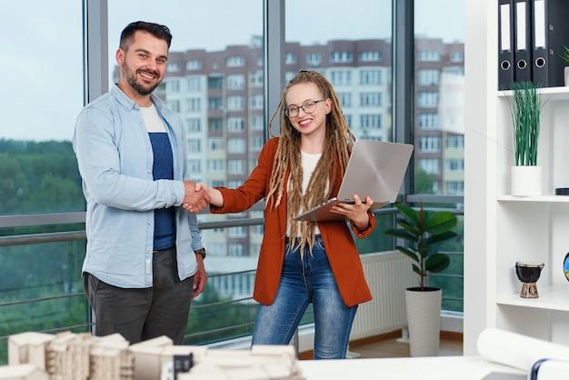 Aangename ervaren moderne stijlvolle tevreden jonge ontwerpers die werkmomenten bespreken met behulp van blauwdruk met project van nieuwe gebouwen in de buurt van panoramisch raam in architectenbureau