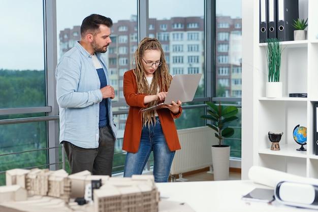 Aangename ervaren tevreden ontwerpers die projectdetails bespreken met behulp van laptop en handshaking