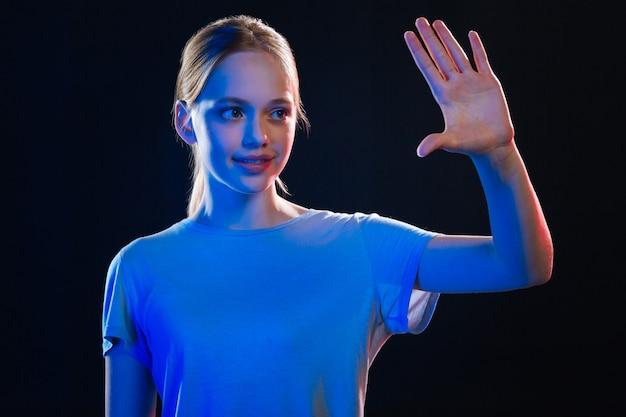Aangename ervaring. opgetogen positieve vrouw die lacht terwijl ze naar haar hand kijkt die tegen het transparante scherm wordt gedrukt