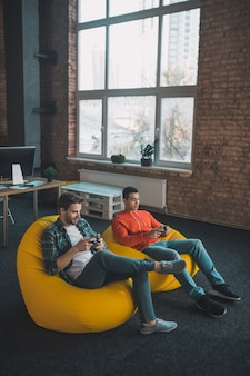 Aangename gelukkige mannen die samen videogames spelen terwijl ze thuis ontspannen
