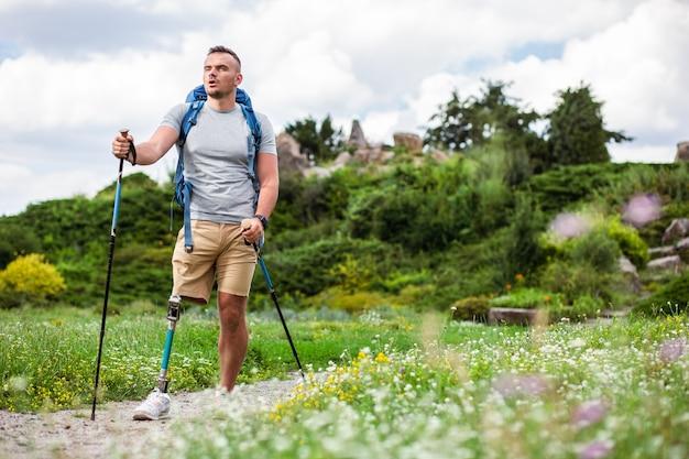 Aangename gemotiveerde man met een handicap die een nordic walking-training volgt en tegelijkertijd zijn gezondheid verbetert