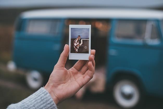 Aangename herinneringen. close-up van een jonge vrouw die een foto van een jong stel vasthoudt terwijl ze buiten staat in de buurt van het blauwe minibusje in retrostijl