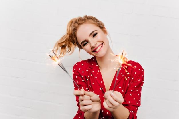 Aangename jonge dame in rode kledij met bengaalse lichten. indoor foto van opgewonden meisje met golvend blond haar nieuwjaar vieren.