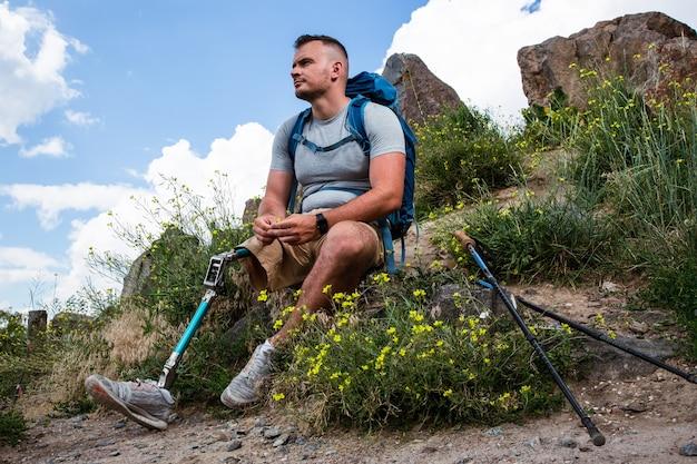 Aangename jonge man met prothese genieten van frisse lucht tijdens het rusten na nordic walking