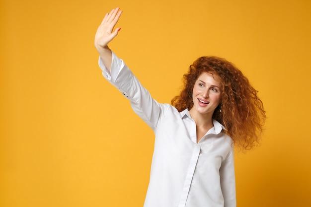 Aangename jonge roodharige vrouw meisje in casual wit overhemd poseren geïsoleerd op geel oranje muur