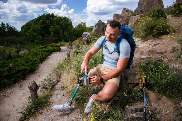 Aangename jonge sportieve man met prothese die thee drinkt tijdens het rusten na een lange wandeling