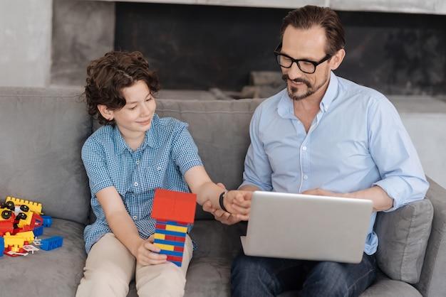 Aangename jonge vader zittend op de bank met zijn laptop op schoot en de hand van zijn zoon aanraken met een toren gebouwd met blokenset