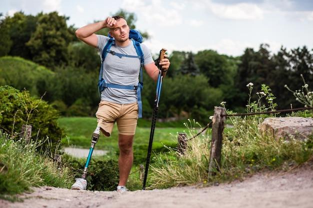 Aangename jonge vermoeide man die behoefte heeft aan een pauze terwijl hij nordic walking probeert