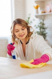 Aangename jonge vrouw die lacht terwijl ze een aanrechtblad schoonmaakt met een speciaal reinigingsmiddel