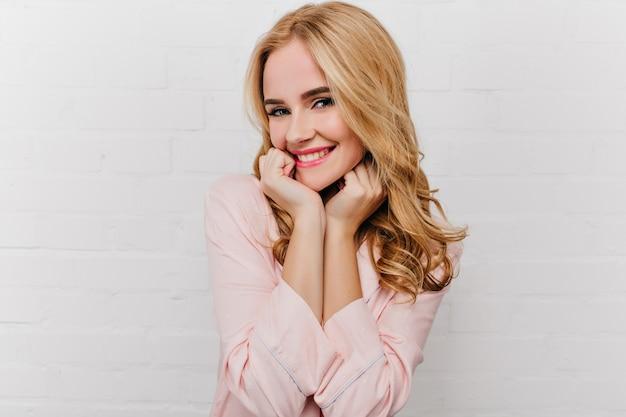 Aangename jonge vrouw die met trendy kapsel op witte muur glimlacht. zalig bleek meisje in roze pyjama's die vroeg in de ochtend thuis stellen.