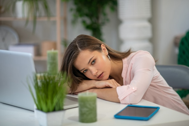 Aangename jonge vrouw die naar de kaars kijkt terwijl ze moe is van het werk