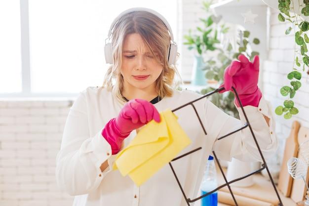 Aangename jonge vrouw die naar het vuile detail van het gasfornuis kijkt terwijl ze het wil schoonmaken