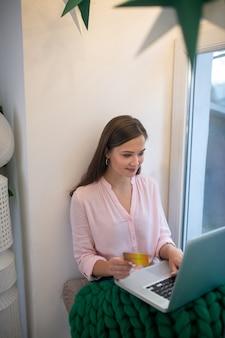 Aangename jonge vrouw die wordt bedekt met een warme deken terwijl ze online verschillende kleding koopt