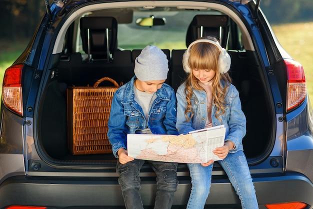 Aangename jongen en meisje kijken in de kofferbak van de auto naar de wegenkaart en bespreken de bewegingsrichting.