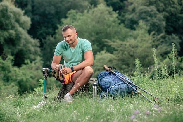 Aangename lachende man met prothese die buiten verfrissend drankje drinkt terwijl hij buiten rust