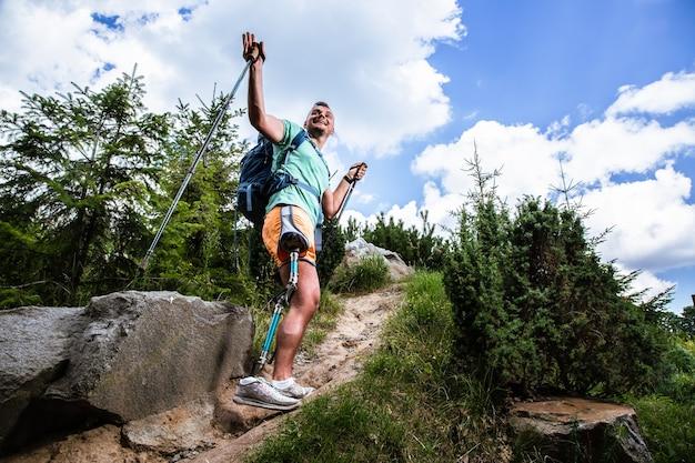 Aangename lachende man met prothese die nordic walking probeert terwijl hij zich gelukkig voelt