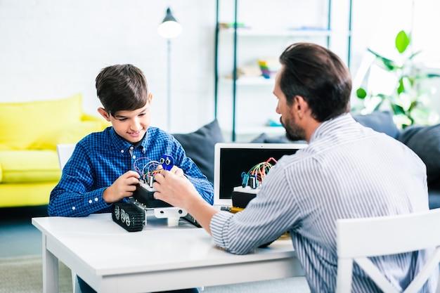 Aangename man en zijn slimme zoon bouwen robot terwijl ze aan tafel zitten