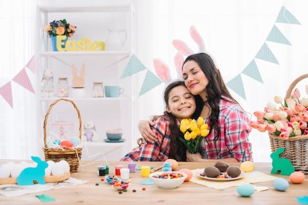 Aangename moeder die haar dochter omhelst die dag van pasen viert