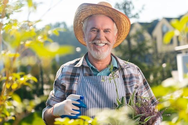 Aangename momenten. betrokken gepensioneerde man die zich geïnspireerd voelt terwijl hij geniet van een dag in de tuin
