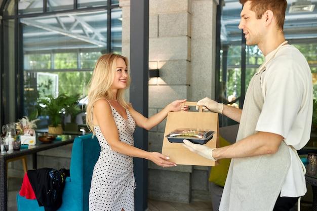 Aangename oberman geeft bestellingen in pakket aan vrouwelijke klant