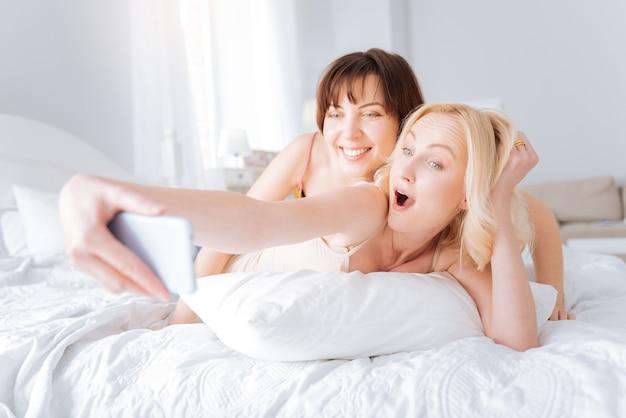 Aangename ochtend. leuk vrolijk vrouwelijk stel dat op het bed ligt en selfies neemt terwijl ze in een geweldige bui zijn