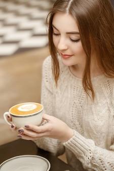 Aangename ochtend. verticale portret van een mooie brunette met een kopje koffie in het café