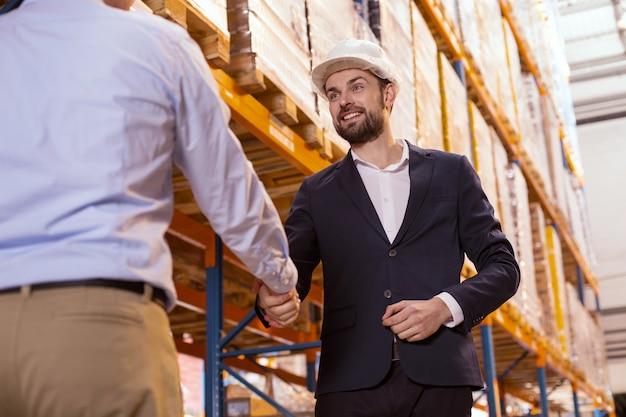 Aangename ontmoeting. opgetogen positieve zakenman die lacht terwijl hij zijn werknemer begroet