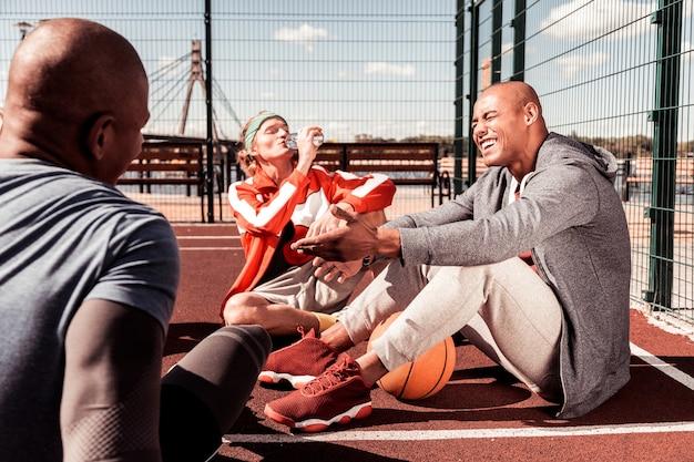 Aangename ontspanning. blije blije mensen praten met elkaar terwijl ze rusten na de training