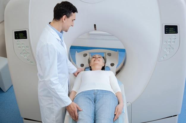 Aangename positieve knappe oncoloog die naast zijn patiënt staat en glimlacht terwijl hij naar haar kijkt