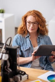 Aangename professionele vrouwelijke ontwerper die een tablet vasthoudt en naar de 3d-printer kijkt terwijl hij aan het werk is
