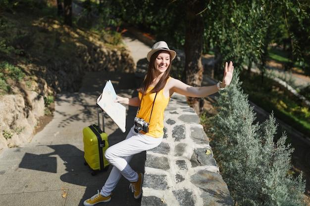 Aangename reiziger toeristische vrouw in hoed met koffer, stadskaart zwaaiende hand voor begroeting, vriend ontmoeten in de stad buiten. meisje dat naar het buitenland reist om een weekendje weg te reizen. toeristische reis levensstijl.