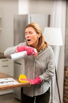 Aangename rijpe blonde vrouw met een allergische reactie op schoonmaakmiddelen