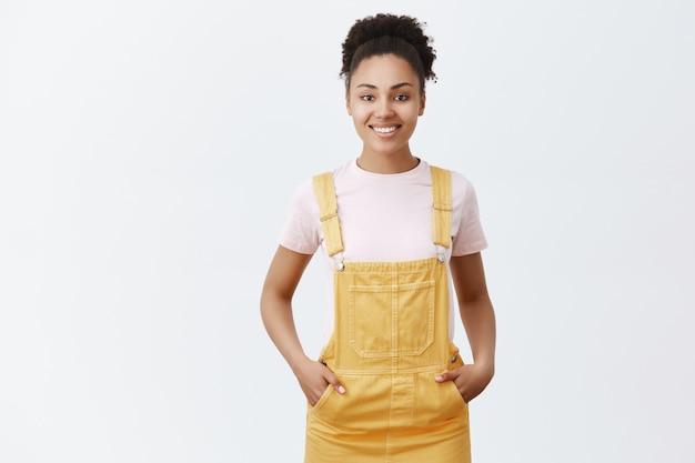 Aangename schattige, donkere vrouwelijke medewerker die klanten helpt bij het vinden van het juiste artikel om te kopen. vrolijk vriendelijk ogend meisje in trendy gele overall, hand in hand in de zakken en lachend