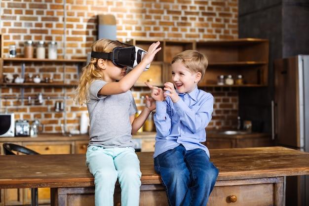 Aangename schattige kleine broertjes en zusjes die een vr-bril gebruiken terwijl ze in de keuken zitten