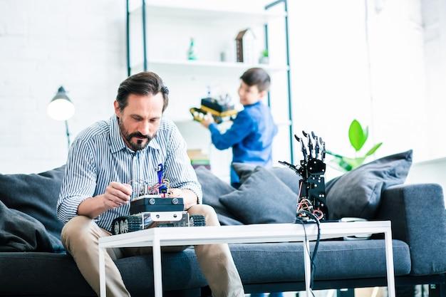Aangename slimme man die een robotapparaat uitwerkt terwijl zijn zoon op de achtergrond staat en nieuwsgierigheid uitdrukt
