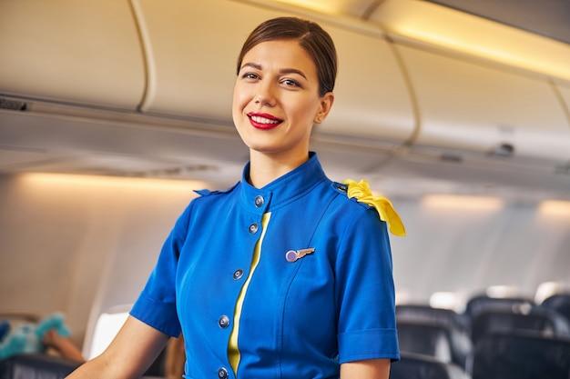 Aangename stewardess staande op een vliegtuig gangpad