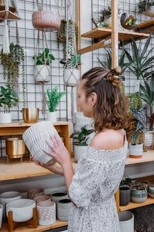 Aangename tijd om te winkelen in offline winkel jonge vrouw in schattige jurk koopt bloempot in winkel