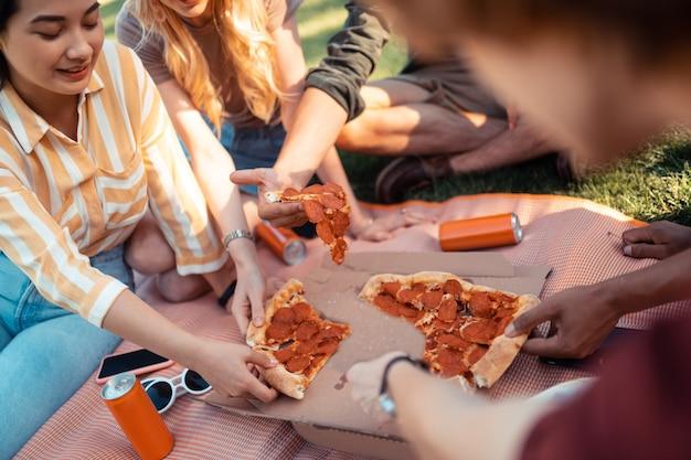 Aangename tijdsbesteding. gelukkige vrienden zitten dicht bij elkaar op het grasveld en pizza eten in de frisse lucht.