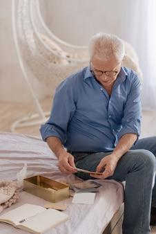 Aangename trieste senior man die oude brieven omdraait en zich zijn verleden herinnert terwijl hij op het bed zat