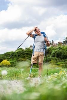 Aangename vermoeide gehandicapte man die nordic walking probeert tijdens een actief weekend