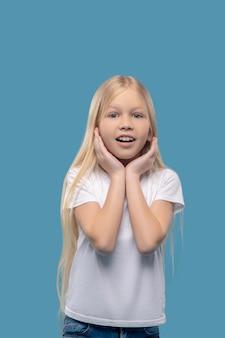 Aangename verrassing. klein blij verrast blond meisje met handen in de buurt van yena gezicht tegen lichte achtergrond