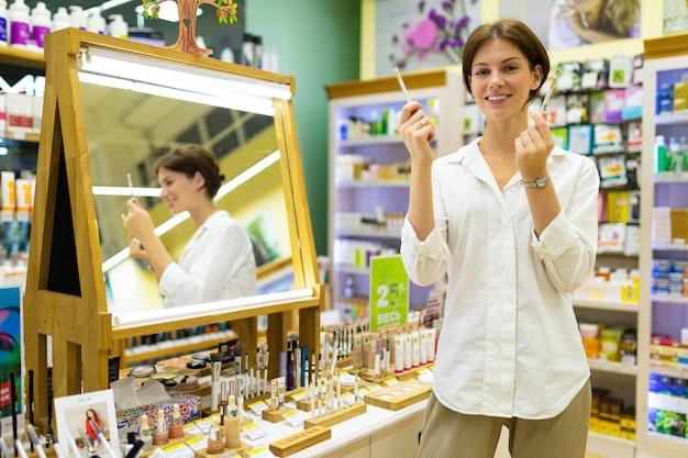 Aangename visagiste demonstreert twee oogpotloden in haar handen