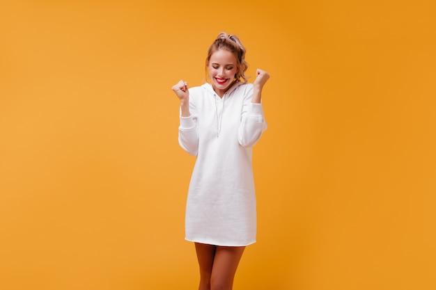 Aangename, vriendelijke blondine in streetstyle-jurk houdt haar handen in vuisten en lacht