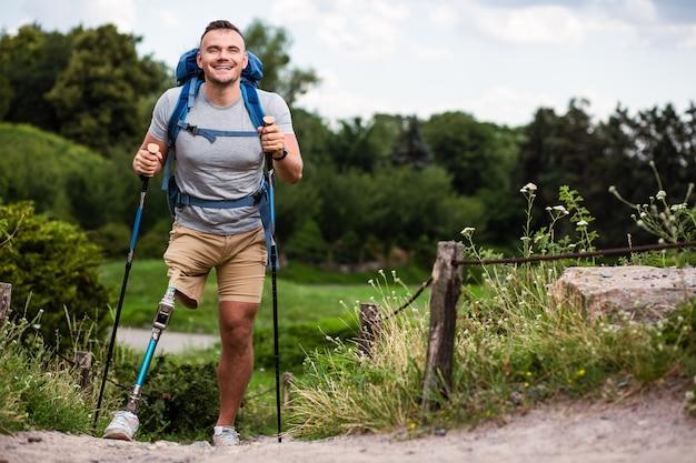Aangename vriendelijke mannelijke toerist die nordic walking-stokken vasthoudt terwijl hij zich enthousiast voelt ondanks gezondheidsproblemen
