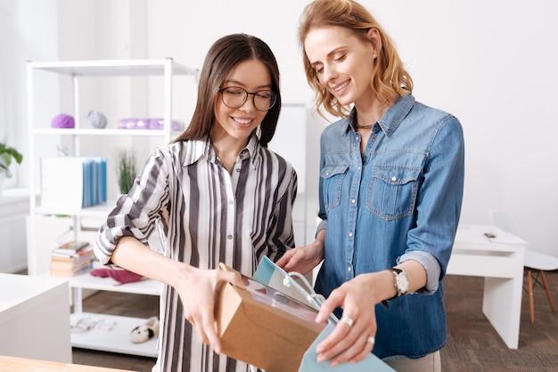Aangename vrolijke ateliermedewerker die een doos met een jurk in een blauwe tas stopt terwijl haar collega deze tas voor haar vasthoudt