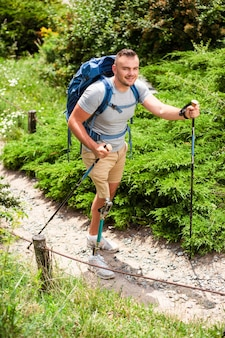 Aangename vrolijke man met een handicap die buiten traint terwijl hij nordic walking uitprobeert